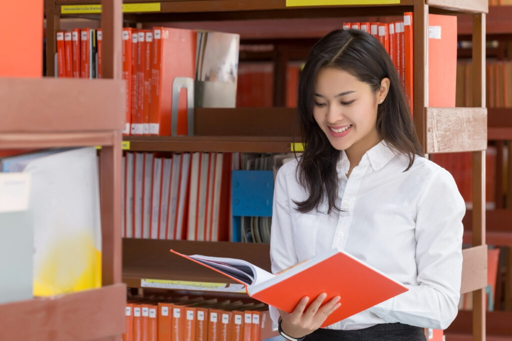 Young business woman reading book in the library.